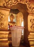 Καταπληκτικό χρυσό άγαλμα του Βούδα στη χρυσή κοιλότητα με την προσφορά ποτών που δίνεται στο Βούδα Στοκ Εικόνες