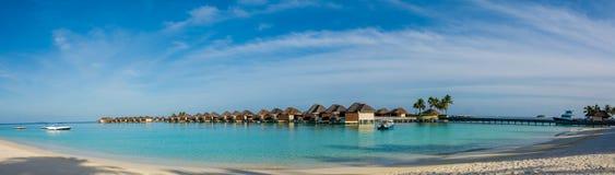 Καταπληκτικό όμορφο τροπικό πανόραμα παραλιών των bungalos νερού κοντά στον ωκεανό με τους φοίνικες και την άσπρη άμμο στις Μαλδί Στοκ φωτογραφία με δικαίωμα ελεύθερης χρήσης