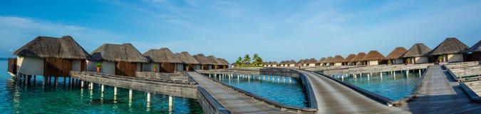 Καταπληκτικό όμορφο τροπικό πανόραμα παραλιών των bungalos νερού με τη γέφυρα κοντά στον ωκεανό στις Μαλδίβες Στοκ Φωτογραφία