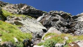 Καταρράκτες που ρέουν στο ειδυλλιακό μη μολυσμένο περιβάλλον που διασχίζει τα πράσινους λιβάδια και τους λίθους στις Άλπεις το κα φιλμ μικρού μήκους