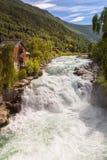 Καταρράκτης, βουνά και σπίτι σε Lom, Νορβηγία στοκ φωτογραφία