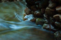 Καταρράκτης και βράχοι με το φύλλο στη σκοτεινή συγκρατημένη και μακροχρόνια έκθεση Στοκ φωτογραφία με δικαίωμα ελεύθερης χρήσης