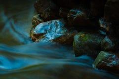 Καταρράκτης και βράχοι με το φύλλο στη σκοτεινή συγκρατημένη και μακροχρόνια έκθεση Στοκ Εικόνα