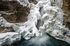 Καταρράκτης που ρέει κάτω από την κάλυψη του χιονιού στα μπλε βάθη στοκ εικόνες