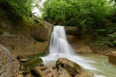 Καταρράκτης σε έναν ποταμό βουνών με το πράσινο πράσινο δάσος νερού και άνοιξη στις τράπεζες στοκ εικόνες