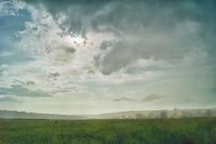 Καταρρακτώδης βροχή και ήλιος σε μια κοιλάδα ενάντια σε ένα σκηνικό των λόφων Στοκ Φωτογραφίες