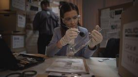 Καταρτισμένη γυναίκα ανώτερος υπάλληλος που παίρνει τα δακτυλικά αποτυπώματα από το μπουκάλι γυαλιού στοιχείων απόθεμα βίντεο