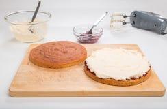 Κατασκευάζοντας τα κέικ σφουγγαριών, κέικ που διαδίδεται με τη μαρμελάδα/την κονσέρβα και buttercream σε έναν ξύλινο πίνακα Στοκ Φωτογραφία