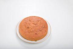 Κατασκευάζοντας τα κέικ σφουγγαριών, μαγειρευμένο κέικ στο πιάτο που απομονώνεται Στοκ Φωτογραφία