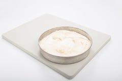 Κατασκευάζοντας το κέικ σφουγγαριών, 1 κασσίτερος κέικ με το κτύπημα κέικ που τίθεται σε μια χλωμή GR Στοκ Εικόνες