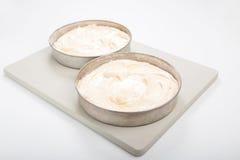 Κατασκευάζοντας το κέικ σφουγγαριών, 2 συσσωματώνουν τους κασσίτερους με το κτύπημα κέικ που τίθεται σε ένα χλωμό γ Στοκ Φωτογραφίες