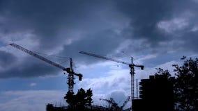 Κατασκευή-γερανοί, ουρανός κάλυψης σύννεφων, πολυόροφο κτίριο οικοδόμησης, σκιαγραφία σπιτιών απόθεμα βίντεο