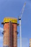Κατασκευή - γερανός και νέα πολυκατοικία πολυόροφων κτιρίων Στοκ Εικόνες