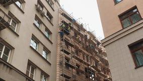 Κατασκευή επισκευής έννοιας υλικών σκαλωσιάς οι εργαζόμενοι κάνουν τις επισκευές στην πρόσοψη του κτηρίου οι εργαζόμενοι κάνουν τ απόθεμα βίντεο