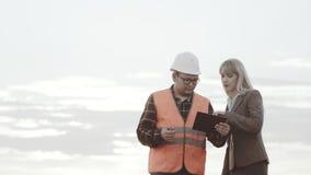 Κατασκευή και διαχείριση της δυνατότητας Επιχείρηση κατασκευής και νέοι Ένας ανάδοχος σε μια αντανακλαστική φανέλλα απόθεμα βίντεο