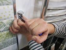 Κατασκευή και επισκευή - ένα επαγγελματικά εργαλείο και ένα κατσαβίδι στα χέρια του οικοδόμου στοκ εικόνες με δικαίωμα ελεύθερης χρήσης