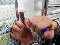 Κατασκευή και επισκευή - ένα επαγγελματικά εργαλείο και ένα κατσαβίδι στα χέρια του οικοδόμου στοκ εικόνες