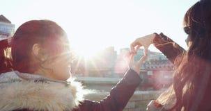 Κατασκευή μιας καρδιάς Δύο χαρωπά αδελφές που κάνουν μια μορφή καρδιών με τα χέρια Εξετάζουν την καρδιά και το χαμόγελο Έννοια απόθεμα βίντεο