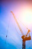 Κατασκευή που ανυψώνει τη σκιαγραφία γερανών ενάντια στο μπλε ουρανό Στοκ Εικόνα