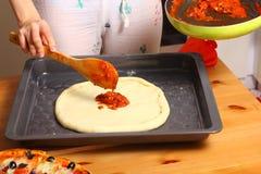 Κατασκευή της πίτσας από τα θηλυκά χέρια στον πίνακα κουζινών Στοκ εικόνες με δικαίωμα ελεύθερης χρήσης