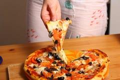 Κατασκευή της πίτσας από τα θηλυκά χέρια στον πίνακα κουζινών Στοκ εικόνα με δικαίωμα ελεύθερης χρήσης