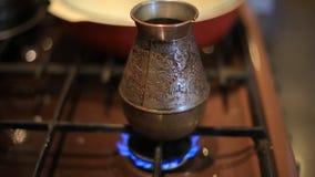 Κατασκευή του καφέ στο τουρκικό δοχείο καφέ σε μια σόμπα αερίου τρόφιμα και ποτό στο σπίτι απόθεμα βίντεο