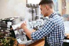 Κατασκευή του καφέ Barista χρησιμοποιώντας τη μηχανή καφέ στον καφέ Στοκ Εικόνα