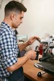 Κατασκευή του καφέ Barista χρησιμοποιώντας τη μηχανή καφέ στον καφέ Στοκ Φωτογραφίες