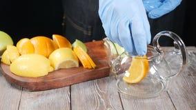 Κατασκευή του τσαγιού φρούτων Ο πυροβολισμός κινηματογραφήσεων σε πρώτο πλάνο bartender δίνει την τοποθέτηση του τεμαχισμένου λεμ απόθεμα βίντεο