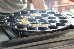 Κατασκευή των τηγανισμένων αυγών ορτυκιών στο καυτό πιάτο στοκ φωτογραφίες