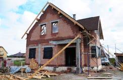 Κατασκευή υλικού κατασκευής σκεπής και οικοδόμηση του νέου κεραμικού σπιτιού τούβλων με τη μορφωματική καπνοδόχο, τους φεγγίτες,  Στοκ φωτογραφία με δικαίωμα ελεύθερης χρήσης