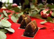 Κατασκευασμένο επιδόρπιο ψηγμάτων σοκολάτας το χρυσό στον πίνακα γαμήλιων επιδορπίων κόκκινου χαλιού με τα πράσινα φύλλα και ρόδι στοκ εικόνες