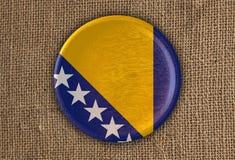 Κατασκευασμένο στρογγυλό ξύλο σημαιών Βοσνίας-Ερζεγοβίνης στο τραχύ ύφασμα Στοκ Εικόνα