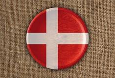 Κατασκευασμένο στρογγυλό ξύλο σημαιών της Δανίας στο τραχύ ύφασμα Στοκ εικόνα με δικαίωμα ελεύθερης χρήσης