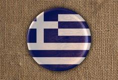 Κατασκευασμένο στρογγυλό ξύλο σημαιών της Ελλάδας στο τραχύ ύφασμα Στοκ εικόνα με δικαίωμα ελεύθερης χρήσης