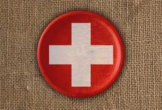 Κατασκευασμένο στρογγυλό ξύλο σημαιών της Ελβετίας στο τραχύ ύφασμα Στοκ φωτογραφία με δικαίωμα ελεύθερης χρήσης