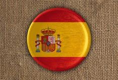 Κατασκευασμένο στρογγυλό ξύλο σημαιών της Ισπανίας στο τραχύ ύφασμα Στοκ Φωτογραφία