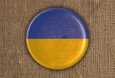 Κατασκευασμένο στρογγυλό ξύλο σημαιών της Ουκρανίας στο τραχύ ύφασμα Στοκ φωτογραφίες με δικαίωμα ελεύθερης χρήσης