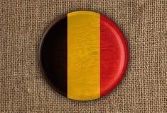 Κατασκευασμένο στρογγυλό ξύλο σημαιών του Βελγίου στο τραχύ ύφασμα Στοκ Εικόνα