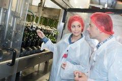 Κατασκευαστές κρασιού που χρησιμοποιούν τα μηχανήματα στο εργαστήριο Στοκ Εικόνες