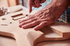 Κατασκευαστής κιθάρων που εργάζεται στο σώμα για την κιθάρα Στοκ Εικόνες