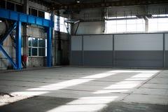 Κατασκευαστικό εργοστάσιο Κενό κτήριο υπόστεγων μπλε ανασκόπησης που τονίζεται Το δωμάτιο παραγωγής με τα μεγάλες παράθυρα και τι Στοκ Φωτογραφία
