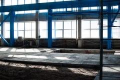 Κατασκευαστικό εργοστάσιο Κενό κτήριο υπόστεγων μπλε ανασκόπησης που τονίζεται Το δωμάτιο παραγωγής με τα μεγάλες παράθυρα και τι Στοκ Φωτογραφίες