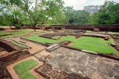 Καταστροφές της αρχαίας πόλης κάτω από το βράχο Sigiriya, Σρι Λάνκα Πάρκο με τα δέντρα και τη archeological περιοχή Περιοχή παγκό Στοκ Εικόνα
