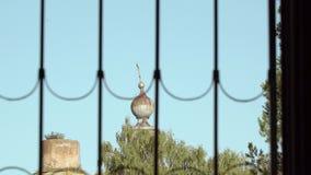Καταστροφές της παλαιάς εκκλησίας μέσω ενός παραθύρου με τους φραγμούς φιλμ μικρού μήκους