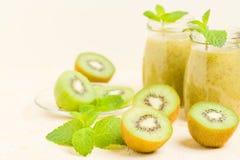 Καταφερτζής ακτινίδιων που διακοσμείται με τα φρέσκα πράσινα φύλλα μεντών και τα ακατέργαστα ώριμα φρούτα περικοπών στο κίτρινο υ στοκ εικόνες με δικαίωμα ελεύθερης χρήσης