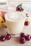 Καταφερτζής κερασιών και μπανανών με τα φρέσκες κεράσια και τις μπανάνες Κεράσι Milkshake μπανάνα milkshake φρέσκα πράσινα φύλλα Στοκ εικόνες με δικαίωμα ελεύθερης χρήσης