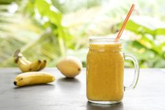 Καταφερτζής με τα τροπικά φρούτα: μάγκο, μπανάνα, ανανάς σε ένα βάζο γυαλιού στον ξύλινο πίνακα r στοκ εικόνες