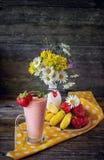 Καταφερτζής μπανάνα-φραουλών με το λευκό με το ζωηρόχρωμο κύπελλο σημείων Πόλκα με τις φράουλες σε μια κίτρινη πετσέτα και ένα βά Στοκ Φωτογραφία