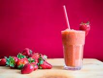 Καταφερτζής φραουλών στο γυαλί με το άχυρο Στοκ Φωτογραφίες